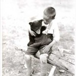 Aboriginal boy holding a bear cub, Prince Albert National Park, c 1928.